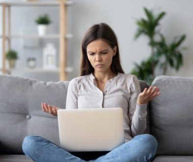 Confused young woman looking on laptop feels bewildered by reading online news