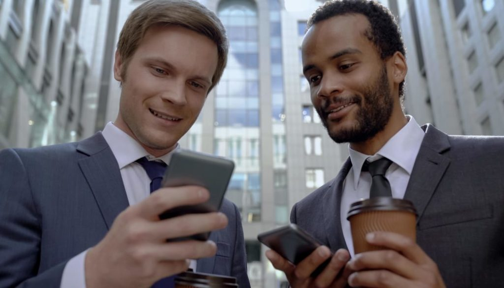 Coworkers having rest on coffee break using mobile app to search
