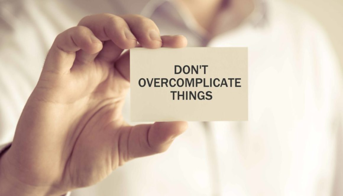 Businessman holding DONT OVERCOMPLICATE THINGS message card