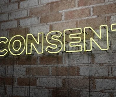 CONSENT - Glowing Neon Sign on stonework wall